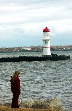 A girl alone on the shore, looking at a lighthouse.