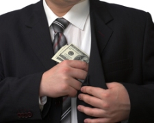 A man putting a bribe into his pocket.
