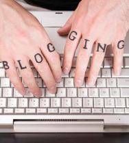 Two hands with BLOGGING written across the knuckles.