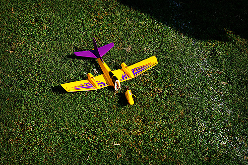 A yellow and purple toy plane that has crashed and broken on green grass.