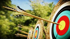 An arrow splitting another arrow on a bullseye target.