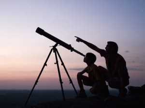 Two people use a telescope to look to the heavens.