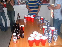 A group is playing / setting up beer pong.