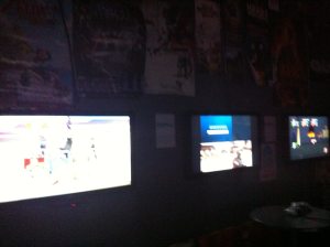 A very dark picture of three screens that made up about half of Melbourne Mana Bar's gaming capabilities.